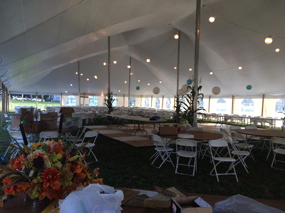 Large outdoor partially enclosed wedding tent with lights, tables, chairs